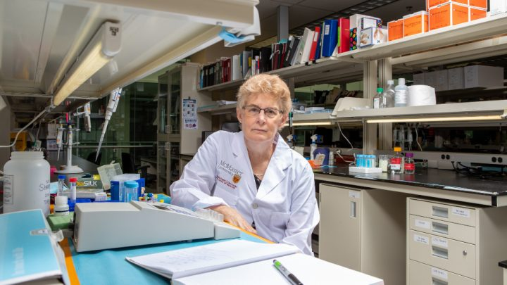 A woman wearing a lab coat sitting in a lab
