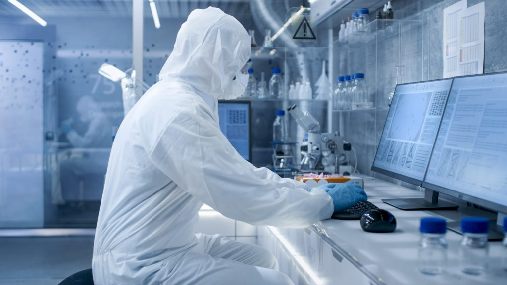 Researcher in full PPE working in a lab